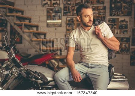 Handsome stylish man is holding his leather jacket and looking away while sitting on the motorcycle in the repair shop