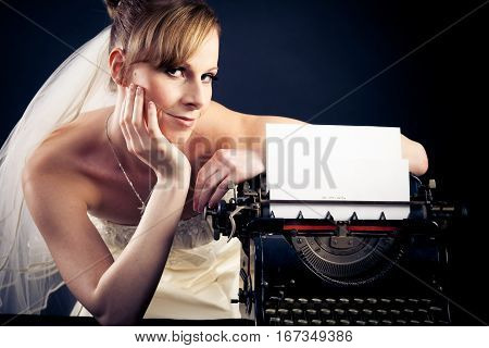 a young, beautiful bride is standing next to a typewriter, the sheet of paper saying 'ich trau mich' german for both 'i am getting married' and 'i dare' . you can easily clone out the writing.