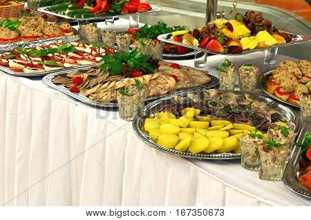 Table with sandwiches snacks appetizers and pickles on a white tablecloth for buffet