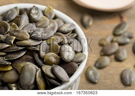 Unshelled pumpkin seeds in white bowl on wooden table background