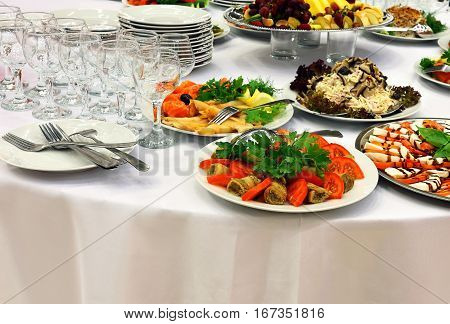 Table with appetizers and pickles on a white tablecloth for buffet