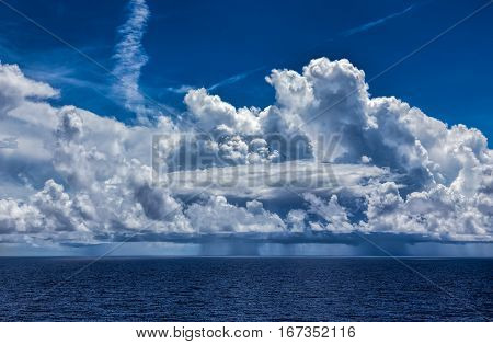 Ocean Thunderstorm with Cumulonimbus clouds and rain. A blue sky surrounds the storm with blue ocean water below.