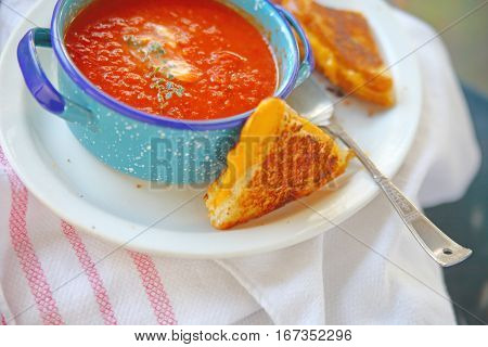 Cup of tomato soup with fresh thyme and grilled cheese sandwich