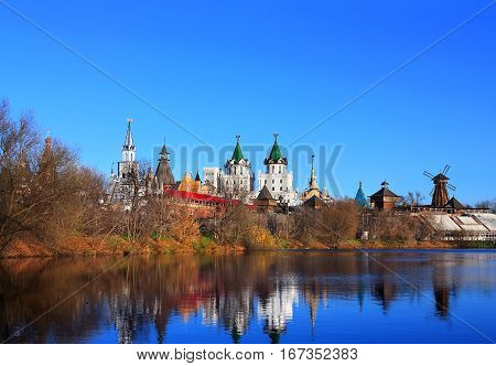 Ancient russian kremlin with colorful towers on the banks of the pond