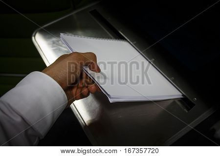 Dropping of paper in a metal bin container for safe disposal of business documents