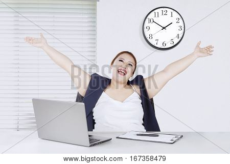 Portrait of beautiful entrepreneur lifting hands while sitting in front of her laptop in the office