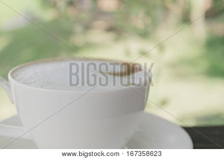 Selective focus white cup of Coffee latte on the wooden table