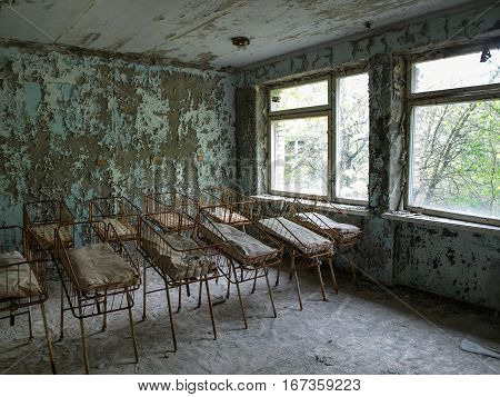 Baby cribs lined up in a building of the ghost town Pripyat in the Chernobyl Exclusion Zone which was established after the nuclear disaster in 1986