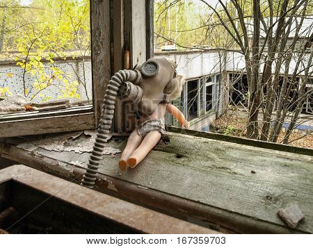 Doll with a gas mask on a window board in the ghost town Pripyat in the Chernobyl Exclusion Zone which was established after the nuclear disaster in 1986