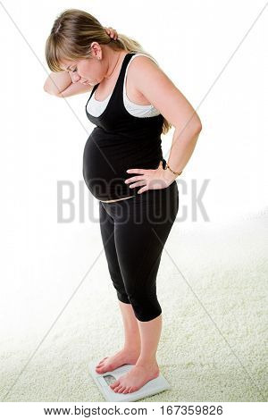 young pregnant woman in a suit for fitness is weighed
