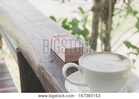 Close Up White Cup Of Coffee, Latte On The Wooden Table With Pink Gift.
