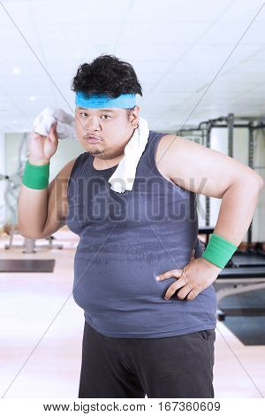 Portrait of overweight young man is wiping sweat with a towel after exercise in the fitness center
