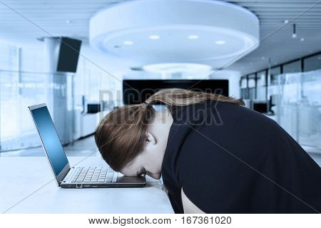 Portrait of female entrepreneur looks tired and feels sleepy while resting on a laptop in the office