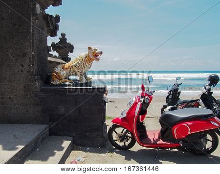 A bright red moped is parked next to a temple with a tiger statue on the beach in Bali Indonesia.