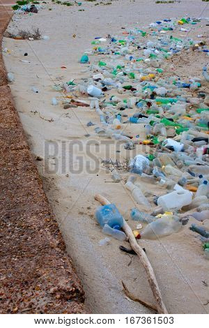 Litter washed up on the beach creating a long line of plastic bottles and other trash.