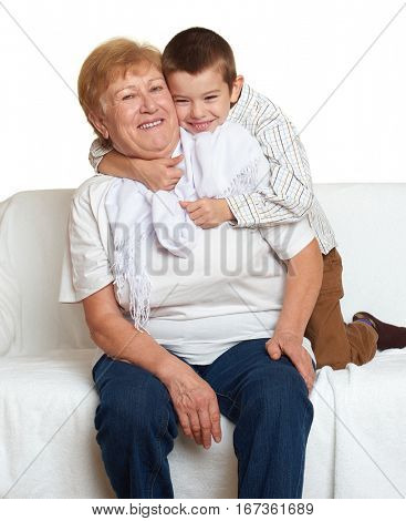 Grandmother and grandchild family portrait on white background, happy people sit on sofa.