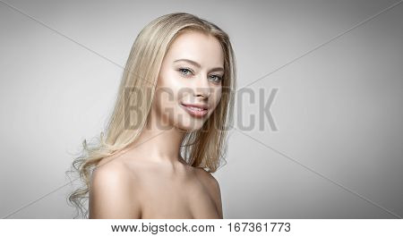 Attractive blonde smiling woman portrait on gray background. Healthy clean skin and perfect makeup on beautiful face of white model with long blonde hair. Beautiful girl. Posing fashion model.