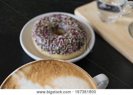 Selective Focus White Cup Of Coffee, Latte On The Wooden Table With Blur Donut Background.
