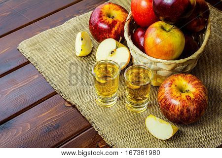 Apple brandy shots and red apples in the rustic wicker basket on wooden background