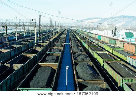 Freight trains with coal at marshalling yard. Cargo wagons at the railway station.