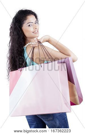Indian female shopper is holding shopping bags while smiling at the camera in the studio