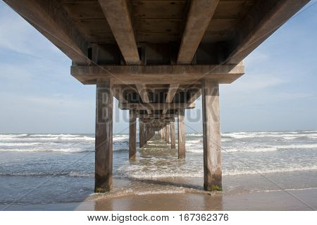 A pier juts into the ocean at the Gulf of Mexico in Texas.