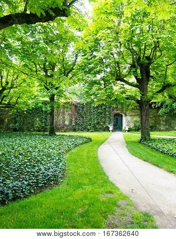 A path leads up to a cute green door in a stone wall evoking image of a secret garden.