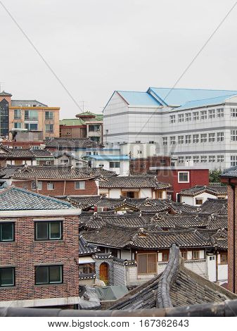 Traditional rooftops of a hanok village in downtown Seoul contrasts with modern skyscrapers in the background.