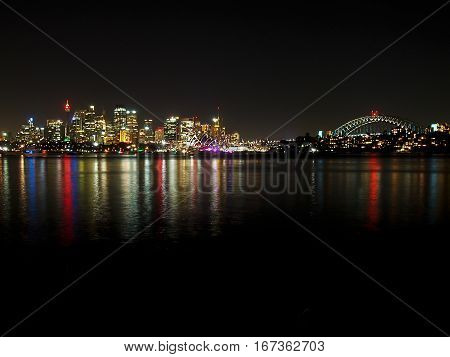 The lights of Sydney reflect in the harbor at night.