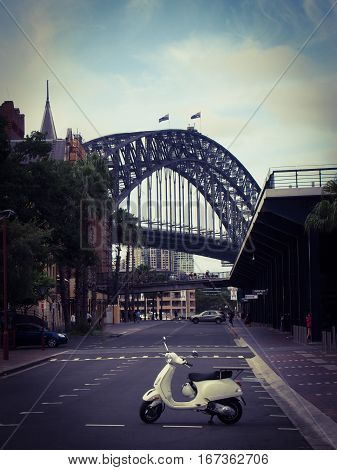 The Sydney Harbor Bridge looms in the background of this street scene of a moped.