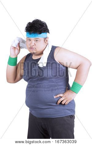 Image of obese young man wiping his body with towel after training in the studio