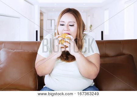 Obese woman eating delicious cheeseburger while sitting on the brown chair