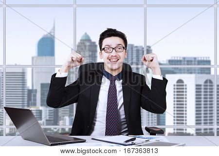 Arabian entrepreneur raising hands and sitting in the office while working with laptop and paperwork on the desk