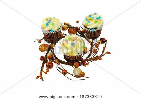 A Spring-themed creative food presentation of cupcakes on a nest decoration. The focus is on the cupcake near the front.