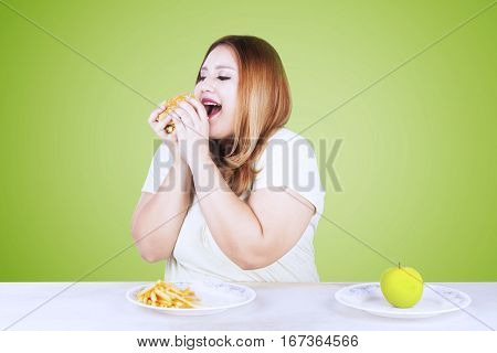 Overweight woman woman refuse to eat apple fruit and choose to eat a junk food