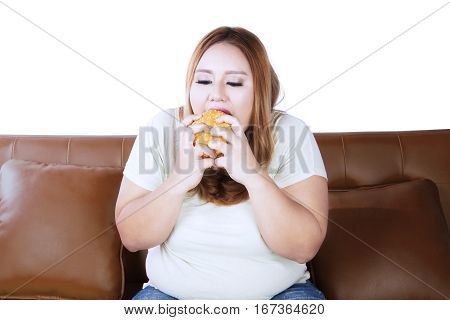 Portrait of overweight woman starving and eating hamburger while sitting on the couch