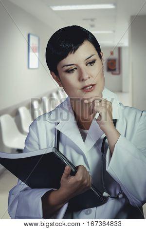 thoughtful brunette female doctor on duty at the ER hospital lobby