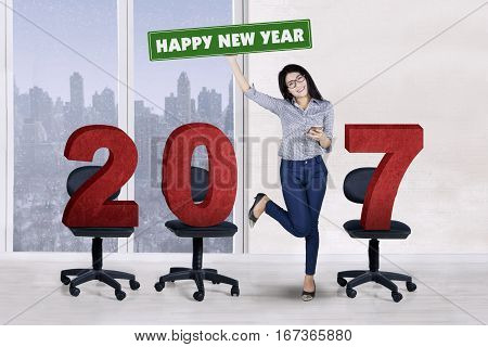 Full length of young entrepreneur standing with number 2017 on the chair while lifting hand winter background on the window