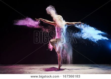 Woman in beige body posing on a tiptoe in cloud of pink and yellow dust streching her arms gracefully