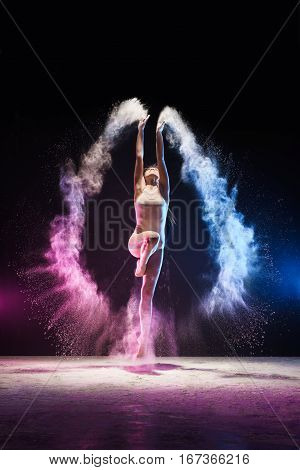 Slender girl jumping and streching her body emotionally in cloud of blue and pink dust studio shot poster