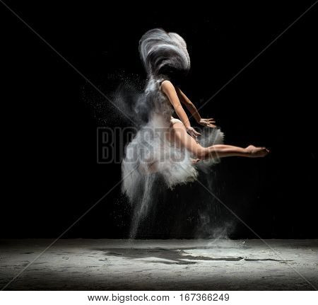 Slender girl dancing in cloud of white studio shot in jump with an effect of the absence of girl s head