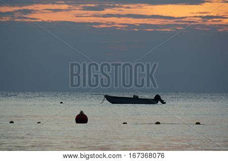 small fishing boat in the sea, almost night,