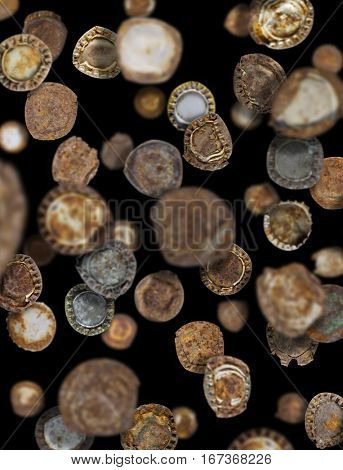 Lots of old rusty bottle caps falling like rain on a black background