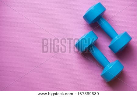 dumbbell and yoga mat on a table