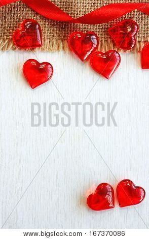 Valentine's day background red ribbon clear glass heart on white board