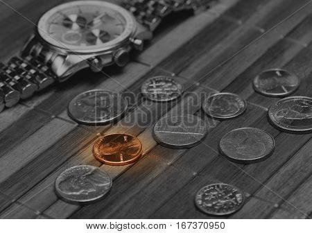 Watch with coins. Cost-is-no-object time is money poor income concept. Black and white image with colored part. Low aperture shot focus on colored coin