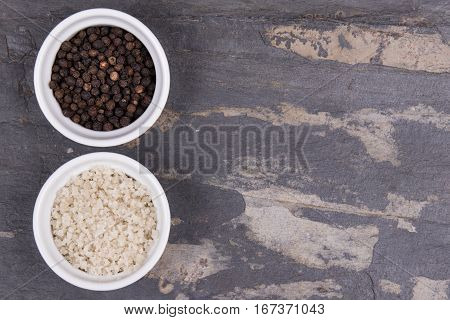 Course Gray Salt And Peppercorns In Smal Ramekins On Gray Slate