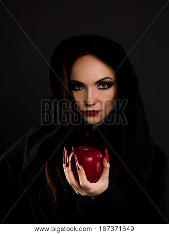 Stepmother in black hoody witch gives poisoned red apple