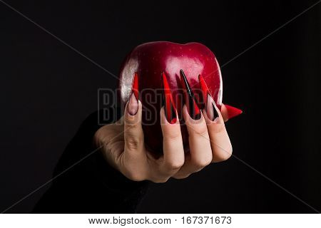 Hands with scary nails manicure holding red apple isolated on black background