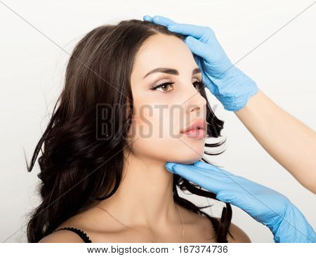 Closeup of Beautiful young woman gets injection in eye and lips area from beautician. preservation of beauty concept.